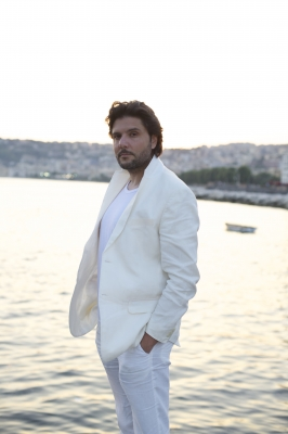 Massimo at the sea with white suite